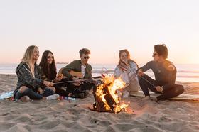 Teenagers on a beach by a bonfire
