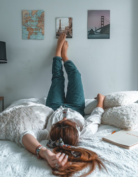 woman lying on bed with legs up wall