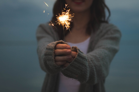 Woman holding a sparkler out in front of her