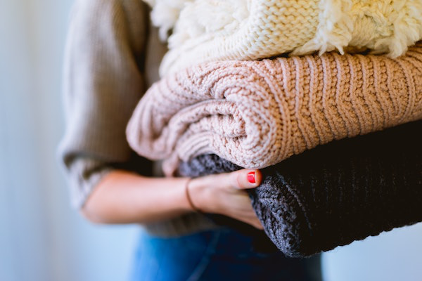 Person With Painted Nails Holding a Stack of Folded Sweaters